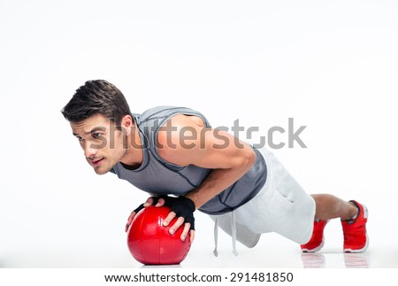 Sports man working out with fitness ball isolated on a white background - stock photo
