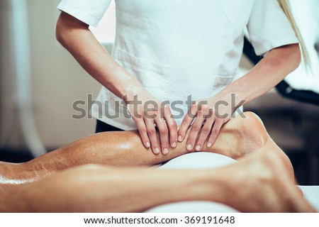 Sports Massage. Massage therapist working with patient, massaging his calves. Toned image. - stock photo