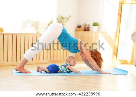 sports mother is engaged in fitness and yoga with a baby at home  - stock photo