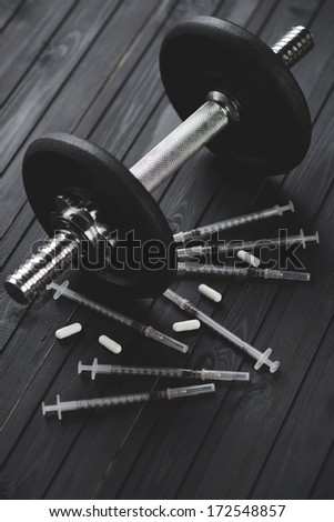 Sports pharmacology concept: dumbbell, syringes and tablets over dark wooden background