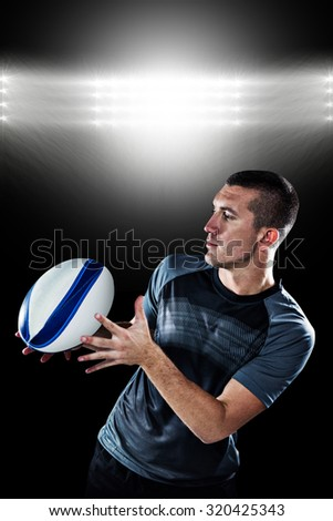 Sports player catching the ball against spotlight