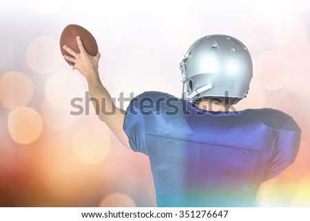 Sports player holding ball against blue glowing background