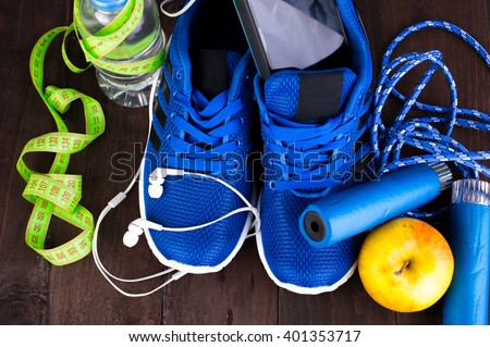 Sports Set, blue running shoe, a measuring tape, rope on a wooden table