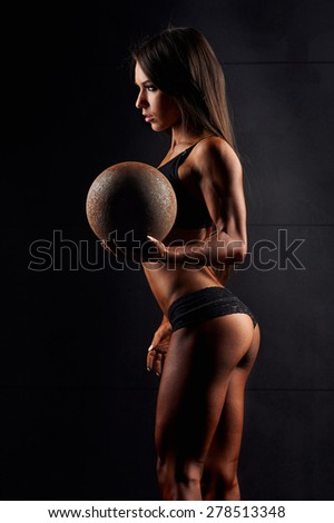 Sports sexy girl with nice abs and toned elastic buttocks in black sportswear. Tanned young sports girl holding a metal ball . The sport of female body. The girl athlete, muscular body. Miss bikini - stock photo