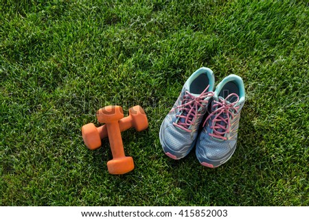 Sports shoes sneakers and pair of orange dumbbells on grass. Fitness training in the open air.