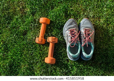 Sports shoes sneakers and pair of orange dumbbells on grass. Sport equipment top view. Sports in the open air. Weights for a fitness training.