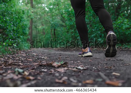 Sports shoes walking or jogging on green grass, man runner cross country running on trail in summer forest. Athlete male training and doing workout outdoors in nature. Jogging workout fitness concept.