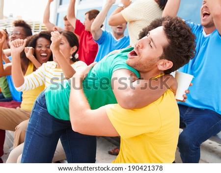 Sports Spectators In Team Colors Celebrating - stock photo