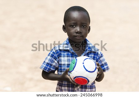 Sports Symbol: Little Black African Soccer Boy Playing With Ball - stock photo
