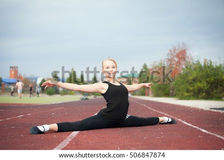 Sports teenage girl in the stadium performs gymnastic exercises