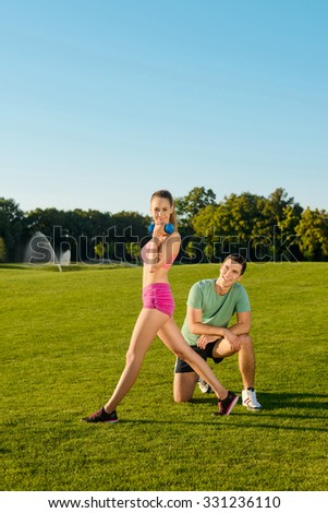 Sports trainer is engaged in fitness with girl outdoors. Fitness on the grass. Sports on the nature. Healthy lifestyle.