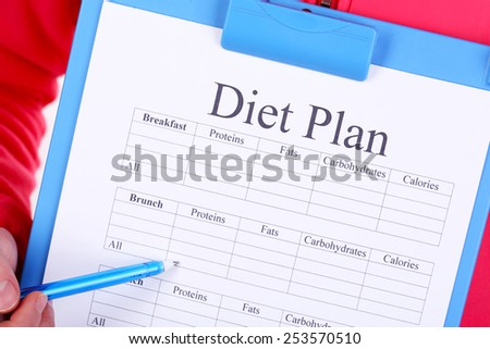 Sports trainer with diet plan close-up - stock photo