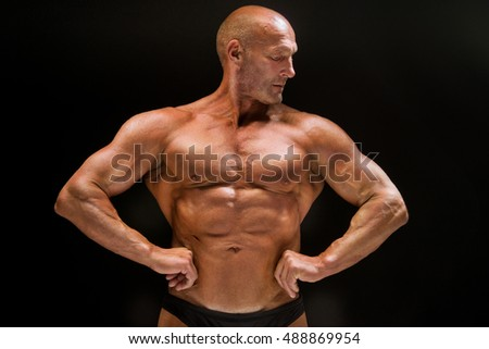 Sports training bald man bodybuilder shows muscles of the chest and press, studio dark background