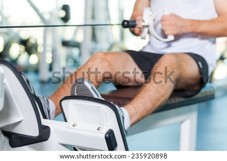 Sports training. Close-up of young man working out in gym - stock photo