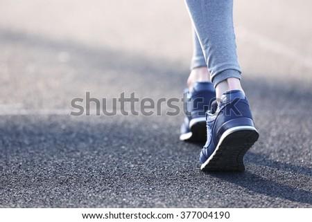 Sports woman legs in running movement - stock photo