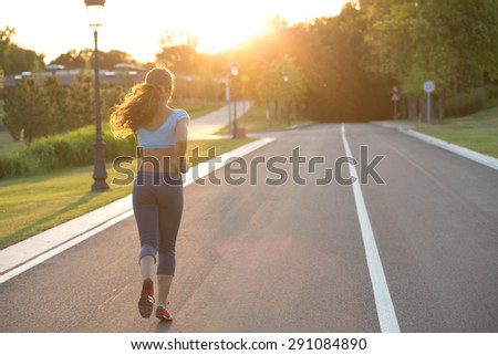 Sports woman running along the road. Long-haired woman supporting healthy lifestyle. - stock photo