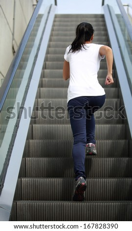 sports woman running on escalator stairs  - stock photo