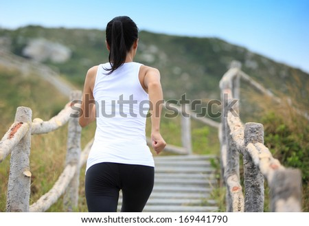 sports woman running on mountain stairs  - stock photo