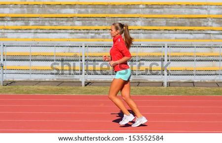 Sports woman running on tracks  - stock photo