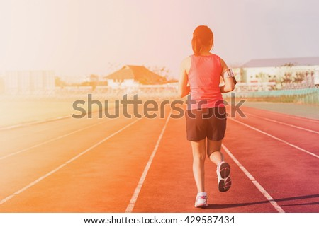 Sports woman running on tracks. Female jogging. Woman jogging on sunset. Fitness health. - stock photo