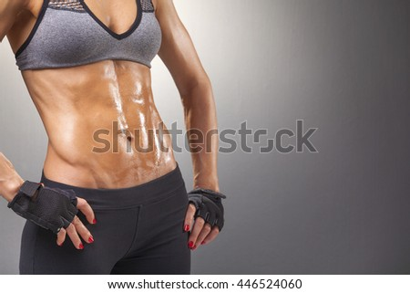 Sports woman with muscular torso on grey background
