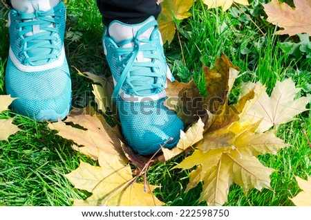 sports women's shoes a background on yellow leaves