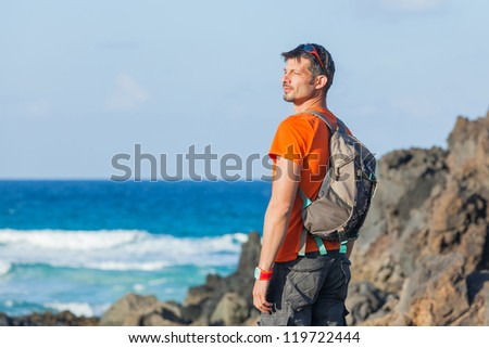 Sports young man with backpack. Background of the sea - stock photo