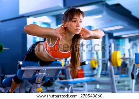 Sports young woman doing exercises on trainer back machine in the gym - stock photo