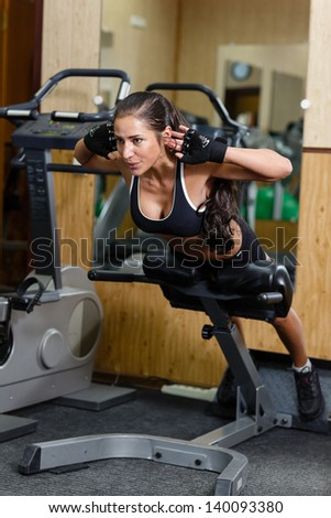 Sports young woman doing exercises on  trainer back machine in the gym. Fitness.