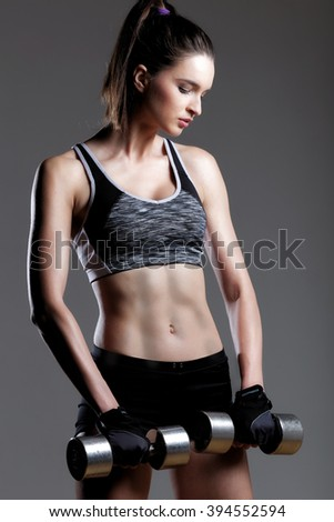 Sports young woman with dumbbells / photo set of sporty muscular female brunette girl wearing sports clothes working out with dumbbell. - stock photo