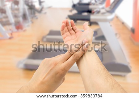 sportsman checking himself the heartbeat in correct way at the gym - stock photo