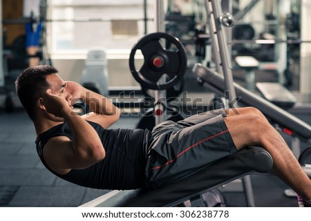 Sportsman doing crunches in the gym - stock photo