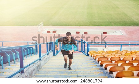 sportsman doing speed exercise for muscles on the stairs on the stadium - stock photo