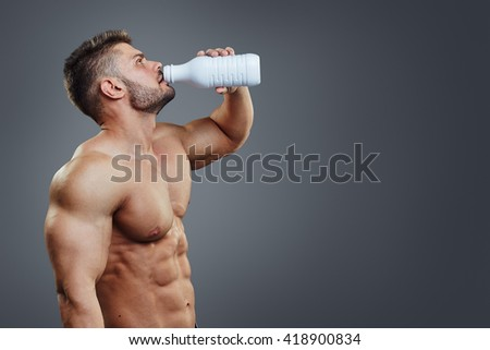 Sportsman drinking milk from a white bottle isolated over a grey background with copyspace. Healthy muscular man drinking protein cocktail - stock photo