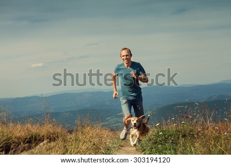 Sportsman has a mountain jogging walk with his beagle dog - stock photo