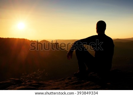 Sportsman hiker in black sportswear sit on mountain top and take a rest with watching down to morning valley.