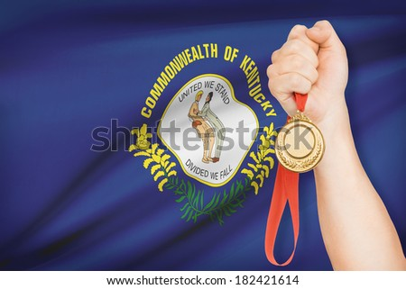 Sportsman holding gold medal with Commonwealth of Kentucky flag on background. Part of a series. - stock photo