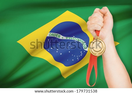Sportsman holding gold medal with flag on background - Federative Republic of Brazil - stock photo