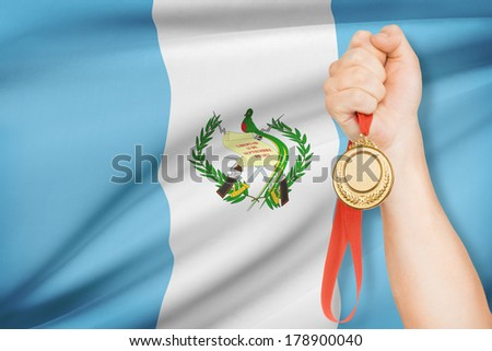 Sportsman holding gold medal with flag on background - Guatemala - stock photo