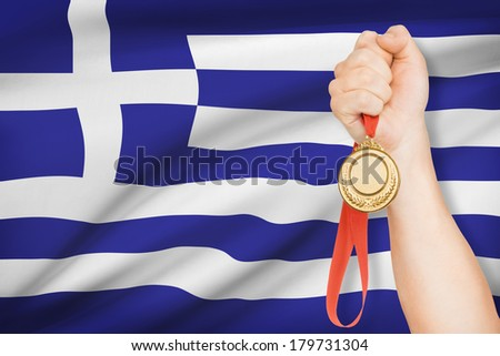 Sportsman holding gold medal with flag on background - Hellenic Republic - stock photo