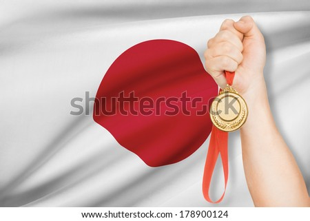 Sportsman holding gold medal with flag on background - Japan - stock photo