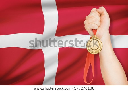 Sportsman holding gold medal with flag on background - Kingdom of Denmark - stock photo
