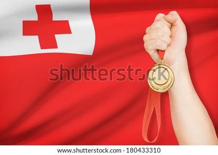Sportsman holding gold medal with flag on background - Kingdom of Tonga - stock photo