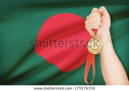 Sportsman holding gold medal with flag on background - People's Republic of Bangladesh - stock photo