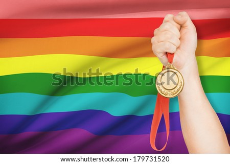 Sportsman holding gold medal with flag on background - Rainbow flag - stock photo