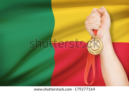 Sportsman holding gold medal with flag on background - Republic of Benin - stock photo