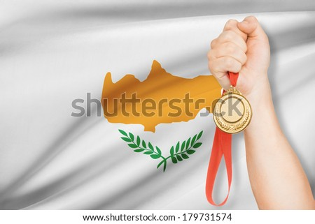 Sportsman holding gold medal with flag on background - Republic of Cyprus - stock photo