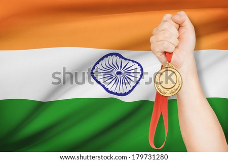 Sportsman holding gold medal with flag on background - Republic of India - stock photo