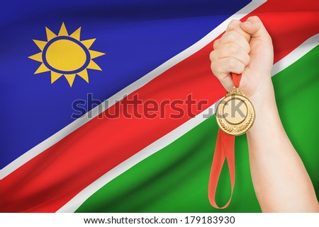 Sportsman holding gold medal with flag on background - Republic of Namibia - stock photo