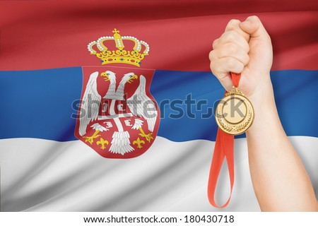 Sportsman holding gold medal with flag on background - Republic of Serbia - stock photo